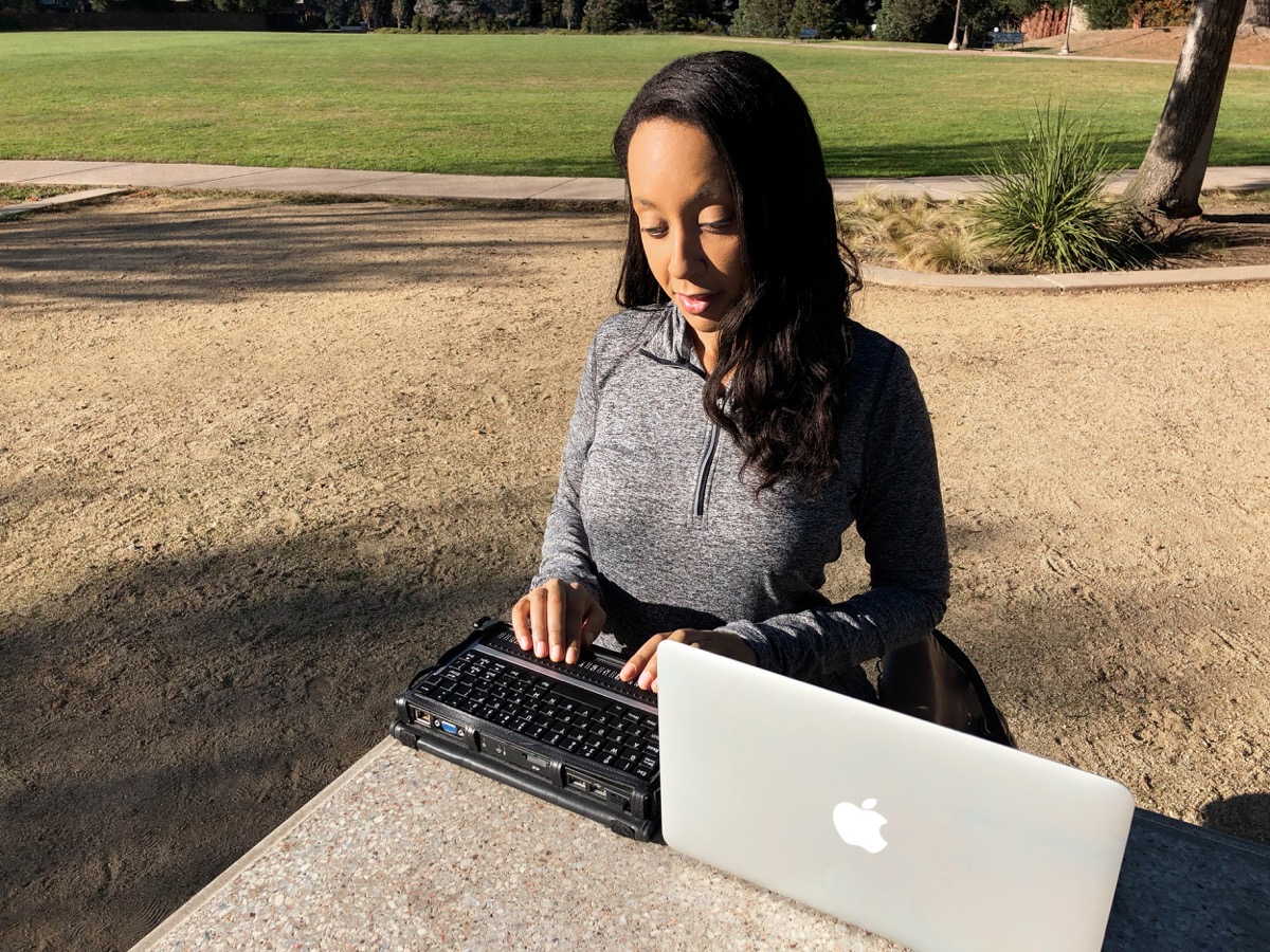 Disability rights lawyer Haben Girma uses MacBook Pro and a braille display to communicate.